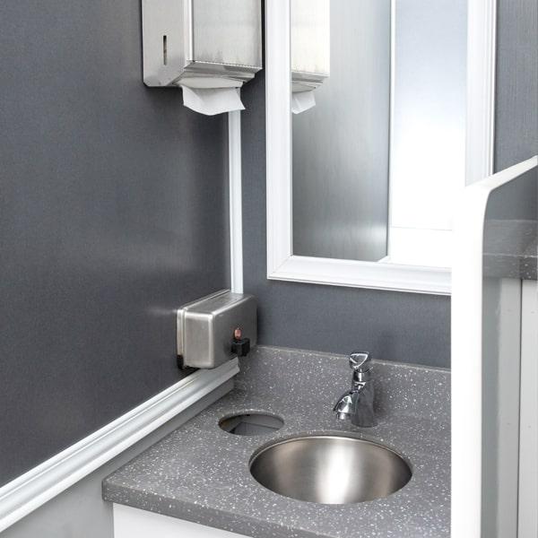 sink with grey countertop inside luxury restroom trailer