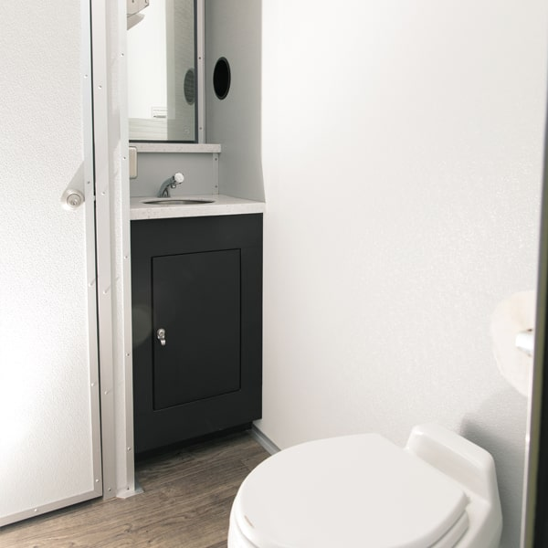 side view of toilet, sink and mirror inside luxury restroom trailer